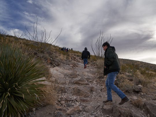 Andrew Castillo, (right), 15, and his step brother Elijah Trujillo, (14) are pictured walking up the trail of Tortugas Mountain on Monday morning during the Fiesta of Our Lady of Guadalupe procession.