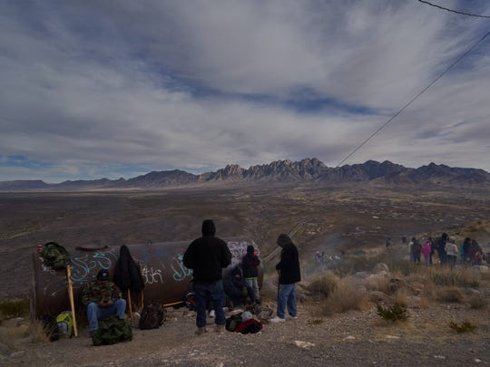Devotees rest after making the hike up Tortugas Mountain on Monday morning during the Fiesta of Our Lady of Guadalupe procession.