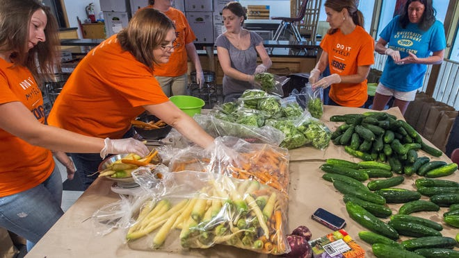 Employees at Kids and Fitness Essex assemble Summer Harvest Bundles on July 24. The bundles featured fresh organic vegetables from the Jericho Settlers Farm and were a fundraiser for the center's playground renovation. Some of the bundles were also being donated to the Burlington Boys & Girls Club and Ronald McDonald House.