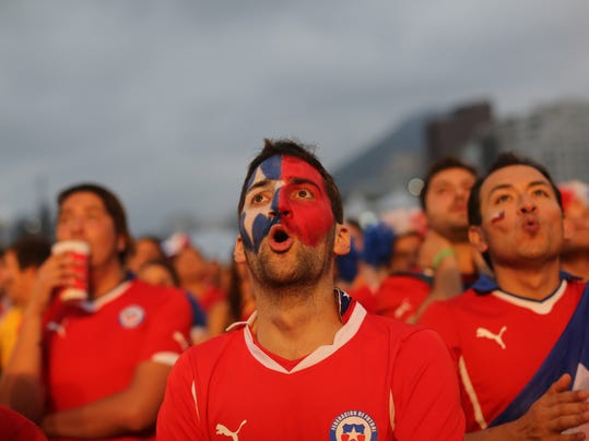 Soccer fans watch a live broadcast of the group B World Cup match between Chile and Spain, inside the FIFA Fan Fest area on Copacabana beach, in Rio de Janeiro, Brazil, Wednesday, June 18, 2014. Chile defeated Spain, the defending champs, 2-0. (AP Photo/Leo Correa)