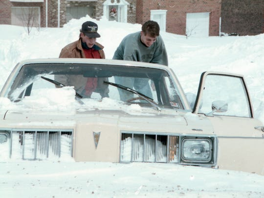 Two men dig out a stranded Pontiac after a blizzard