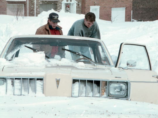 Two men dig out a stranded Pontiac after a blizzard crippled York County in 1993.