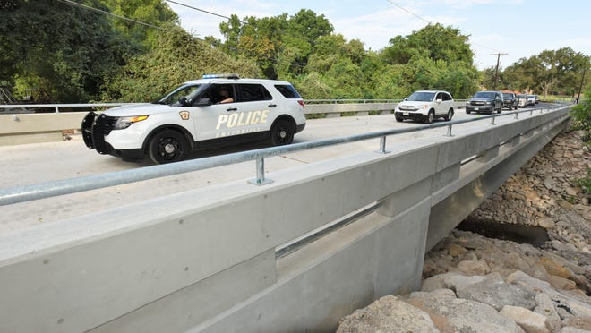 A Smithville police cruiser leads a parade of cars across the new Fourth Avenue bridge on Monday. The replacement of the previous bridge restores two access points for residents of the Mount Pleasant subdivision.