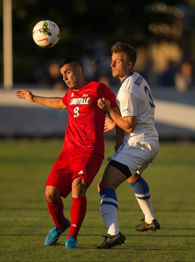 UofL defender Taylor Curtis, left, battles with UK defender Charlie Reymann for control of the ball in the first half. The University of Kentucky hosted the University of Louisville in a soccer match, Tuesday, Sept. 23, 2014 at UK Soccer Complex in Lexington. Photo by Jonathan Palmer, Special to the CJ