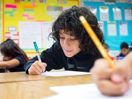 Luis Carlos Miranda, who teacher Brittney Chapman says is one of the better cursive writers in his class, works on a writing assignment at Lowell Elementary School in Mesa.