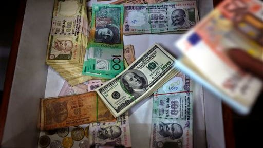 FILE - In this Aug. 22, 2013 file photo, Indian and foreign currency notes lie in a drawer of a foreign currency exchange shop in Bangalore, India. The Treasury Department reports how much foreign buyers adjusted their holdings of U.S. debt in June 2014 on Friday, Aug. 15, 2014.