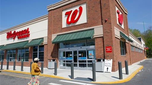 In this May 14 file photo, a customer walks toward the entrance to a Walgreens store in Boston.