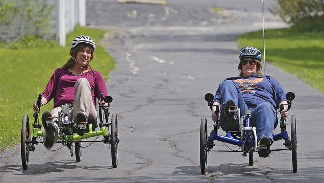 Stroke survivor Michelle Nelson of Little Suamico, right, rides her new recumbent bike to aid in her rehabilitation with Debra Sanchez, Bellin Health Stroke Support Group coordinator, on a feeder trail to the Fox River Trail on Monday, May 9, 2016.