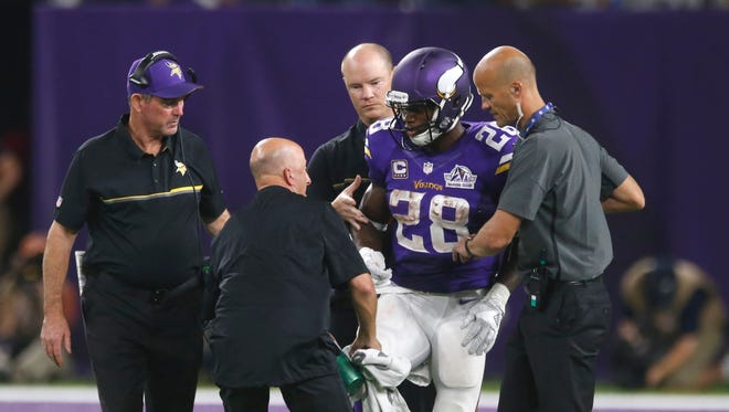 FILE - In this Sept. 18, 2016, file photo, Minnesota Vikings running back Adrian Peterson (28) is helped off the field after getting injured during the second half of an NFL football game against the Green Bay Packers,   in Minneapolis. Peterson will undergo surgery on his right knee to repair a torn meniscus and Vikings coach Mike Zimmer says the star running back could return this season. (AP Photo/Jim Mone, File) ORG XMIT: NY162