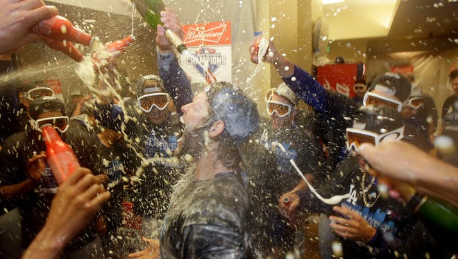 Los Angeles Dodgers pitcher Clayton Kershaw, center, celebrates with teammates in the locker room after the Dodgers beat the San Francisco Giants in San Francisco, on Tuesday. The Dodgers won 8-0 to clinch the National League West division.
