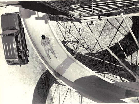 An unknown man rides down the giant water slide at