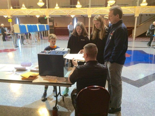 Gov. Steve Bullock is joined by his children Tuesday as he turns in his ballot at the Helena Civic Center.
