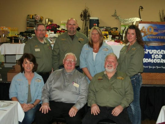 Surrounded by just some of the raffle prizes given away at the Jan. 28 Sturgeon for Tomorrow banquet are chapter officers (front, from left) Treasurer Theresa Mayer, President Dan Groeschel, and Vice President Andy Horn; and (back) Director John Jenkins, Director Brian King, Director Nance Repinski, and Secretary Kris Koenigs.