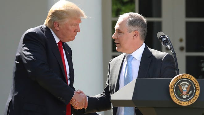 In this June 1, 2017, file photo, President Trump shakes hands with EPA Administrator Scott Pruitt after speaking about the U.S. role in the Paris climate agreement in the Rose Garden.