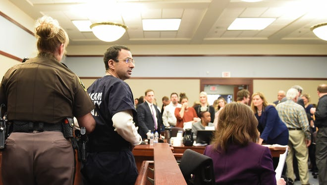 Larry Nassar is escorted out and of circuit court Friday, Jan. 19, 2018, after the fourth day of victim impact statements.