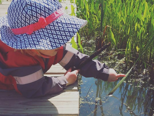 Jessica Featherstone's daughter, Skylar, looks at pond life at the Schlitz Audubon Nature Center.