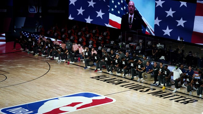 Members of the Toronto Raptors, left, and Boston Celtics listen to the U.S. national anthem prior a basketball game on Friday, Aug. 7, 2020 in Lake Buena Vista, Fla. Boston and Toronto are scheduled to begin a second-round playoff series on Thursday, but Raptors players have discussed boycotting Game 1 of the series in protest of the shooting of Jacob Blake, an unarmed Black man, by police in Wisconsin on Sunday, Aug. 23, 2020.