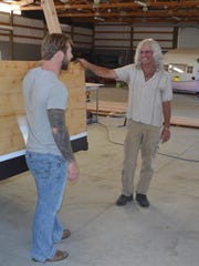 Dillon Davidson shares a laugh with uncle Kerry Elwood as they work on building a wooden houseboat in a cavernous shop space near Turner.
