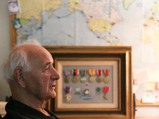 World War II veteran Hank Daub talks about his time in the Army's 10th Mountain Division in front of a frame of medals from his time in the service.