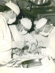 Dr. Norman Halfpenny conducts surgery on the USS Bon