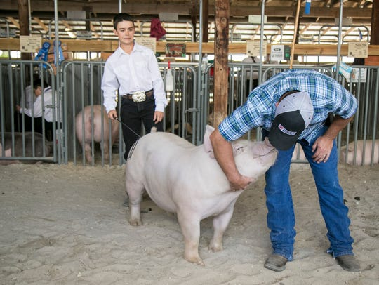 Mike Johns says goodbye to the pig raised by his son, Colton Johns, 13, left, before its turn at the livestock auction at the 2017 Southwest Florida & Lee County Fair.