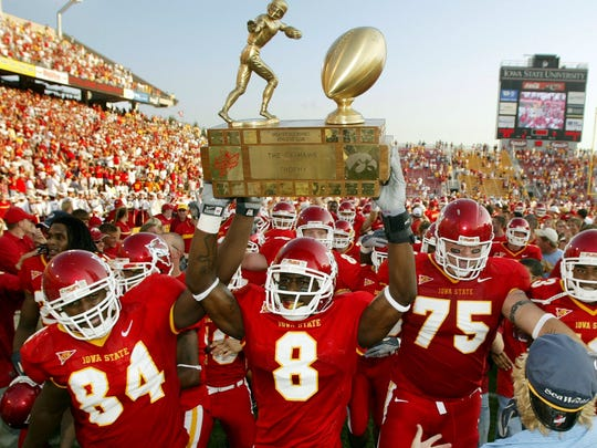 Iowa State's Jason Berryman (84), Steve Paris (8) and Aaron Brant (75) march the Cy-Hawk Trophy back to the locker room after the Cyclones beat the Iowa Hawkeyes, 23-3, Sept. 10, 2005, at Jack Trice Stadium in Ames.