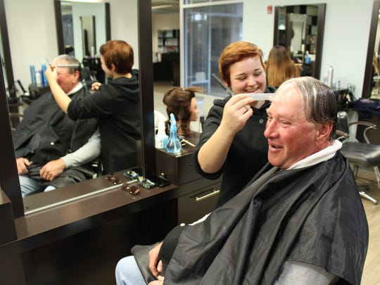 United States Army veteran Randy Fitch receives a complimentary haircut from cosmetology student Caitlyn Hammond on Veterans Day at Tri-Rivers Career Center. The school offered a variety of free services for veterans on Friday.