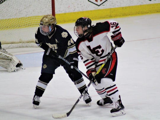Grant Petrucci of Detroit Country Day (left) and Livonia Churchill's Cameron Greener battle for position in front of the Country Day net during the Division 3 state hockey finals on Saturday, March 10, 2018.