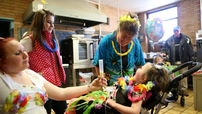 Marie Bentley, in the blue shirt, sings to her granddaughter Layla Martin while Layla's sister Brianna feeds her through a stomach tube during a tropical birthday party in late March. Layla Martin died Saturday at home in Lebanon.