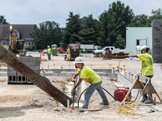 Weddle Brothers Construction crew workers pour concrete as they work in the summer heat at the McCutchanville Elementary School site located just north of McCutchanville Park on Petersburg Road in Evansville, Ind., on Wednesday, July 26, 2017. EVSC Superintendent David Smith said construction is on schedule, and if weather cooperates, the roof will be on around Thanksgiving.