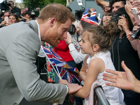 Britain's Prince Harry, left, greets a young well-wisher