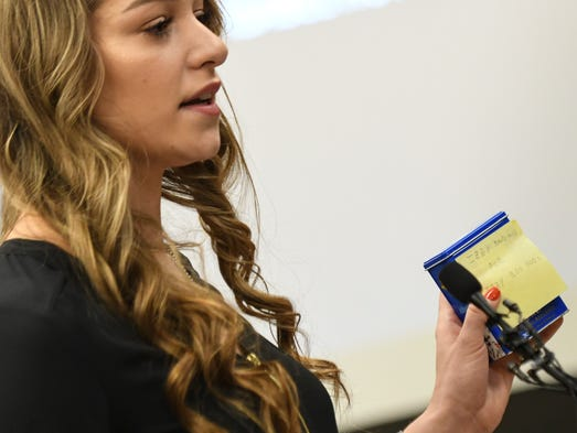 Former gymnast Isabel Hutchins holds up gifts Larry