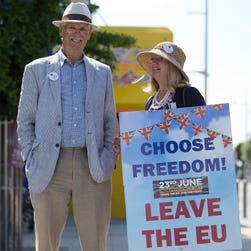 "This file photo taken on June 21, 2016 shows a Leave campaigner holding a placard that reads ""Choose Freedom! Leave the EU"" in Clacton-on-Sea, southern England, as the U.K. Independence Party (UKIP) leader Nigel Farage visits."