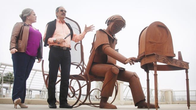 """Columbian artist Edgardo Carmona (right) speaks about his sculpture """"Sintonia"""" at a publicity event for his """"Allure Your Senses"""" exhibit in downtown Fort Myers in January 2016."""
