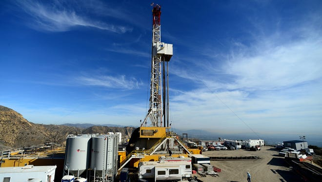 In this Dec. 9, 2015, pool file photo, crews work on stopping a gas leak at a relief well at the Aliso Canyon facility above the Porter Ranch area of Los Angeles.The utility says it has stopped the natural gas leak near Los Angeles after nearly four months.