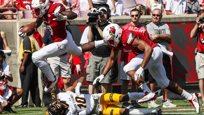 Louisville's Malik Williams jumps over Kent State's Quan Robinson Jr on the way to a touch down in the first quarter.September 23, 2017