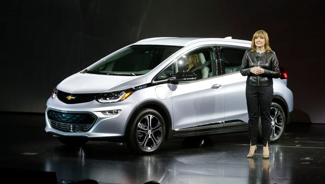 General Motors CEO Mary Barra stands next to the 2017 Chevrolet Bolt EV electric car at CES International, Jan. 6, 2016, in Las Vegas.