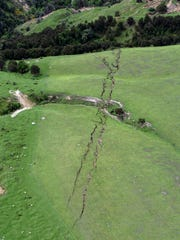 FILE - This Nov. 14, 2016 file photo shows cracks in farmland following a powerful earthquake around Conway near Kaikoura, New Zealand. In terms of human life, the magnitude 7.8 earthquake that hit New Zealand this month was relatively merciful: just two fatalities. But geologically, it moved roads and mountains and even displaced the sea, leaving a formidable mark from which tourism, farming and life in general may need years to recover.