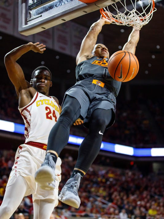 Oklahoma State's Kendall Smith (1) dunks on Iowa State's Terrence Lewis (24) during the second half of an NCAA college basketball game, Tuesday, Feb. 27, 2018, in Ames, Iowa. (AP Photo/Scott Morgan)
