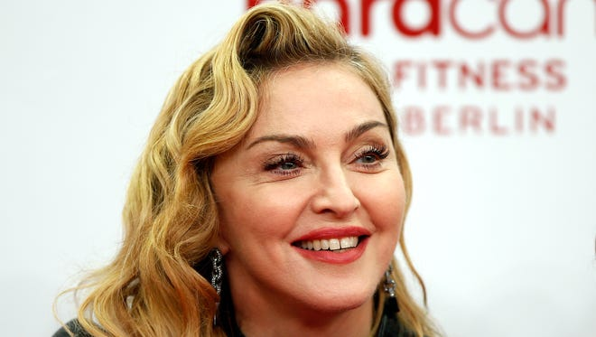 """Madonna smiles during her visit at the """"Hard Candy Fitness"""" center in Berlin in October 2013."""