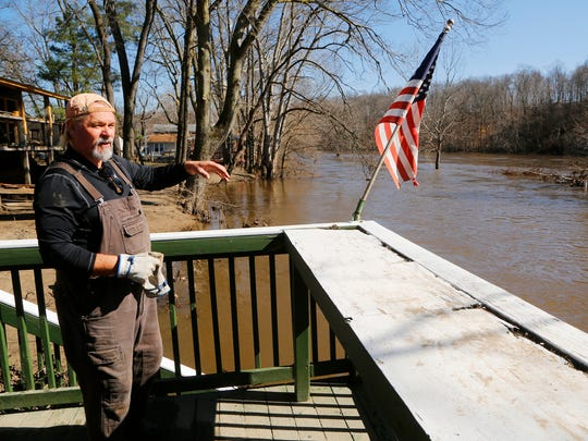 Jeff Seramur looks out at the Tippecanoe River as it flows past his house Monday, February 26, at 11918 Horseshoe Bend Road. Seramur's home, along with many others in the area, suffered significant flood damage after heavy rains last week. Seramur said he can have his home cleaned up in about three weeks. Seramur said he puts up with the flooding because he enjoys seeing nature all around him.