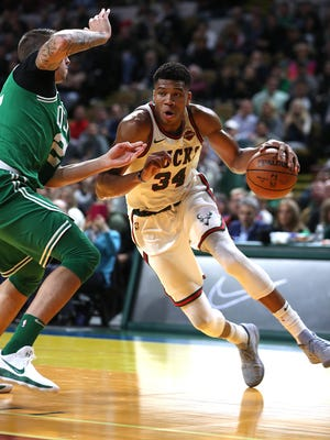 Bucks forward Giannis Antetokounmpo drives past the Celtics'  Daniel Theis in the first half Thursday night at the UW-Milwaukee Panther Arena.