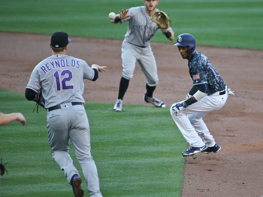 San Diego Padres' Alexei Ramirez is caught in a rundown between Colorado Rockies shortstop Trevor Story and Mark Reynolds  in the second inning of a baseball game Sunday June 5, 2016 in San Diego. (AP Photo/Lenny Ignelzi)