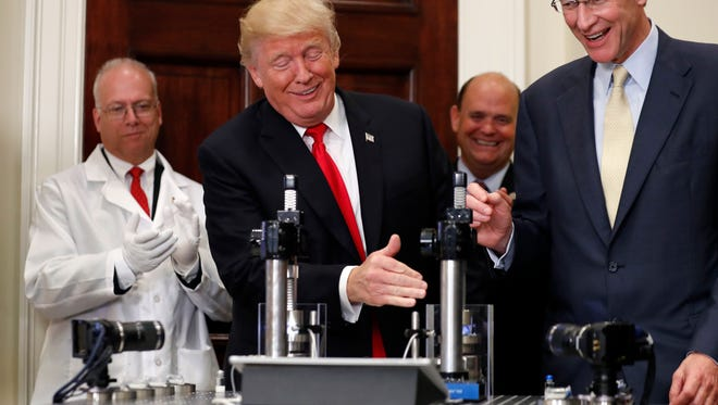President Donald Trump, beside Wendell P. Weeks, right, chairman and CEO of Corning Glass, gets ready to try to crush a Valor Glass protective vial during an event to announce a Merck, Pfizer, and Corning joint partnership at the White House on Thursday.