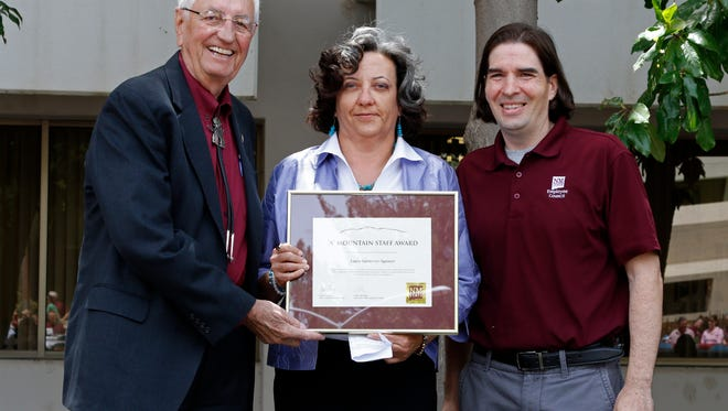 "NMSU Chancellor Garrey Carruthers, left, and Adam Cavotta, chairman of the NMSU Employee Council, presented Laura Gutierrez-Spencer, director of NMSU's Chicano Programs, with the ""A"" Mountain Staff Award during the third annual Founder's Day Picnic Wednesday."