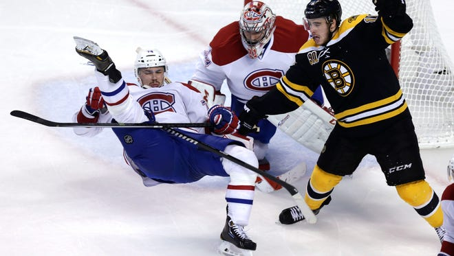 Canadiens defenseman Alexei Emelin, left, is upended by Bruins right wing Reilly Smith, right, in front of goalie Carey Price during the third period in Game 7 on Wednesday.
