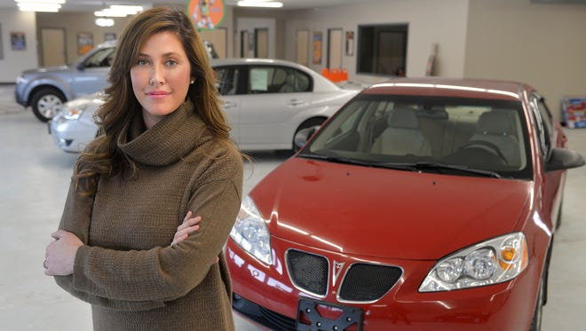 Destini Molitor, CEO of J.D. Byrider in St. Cloud, poses Tuesday, Jan. 19 amid some of the used cars in her new dealership. The dealership is a franchise of an Indiana company that sells used vehicles to customers who usually have a difficult time getting credit. Molitor is also the wife of Minnesota Twins Manager Paul Molitor.