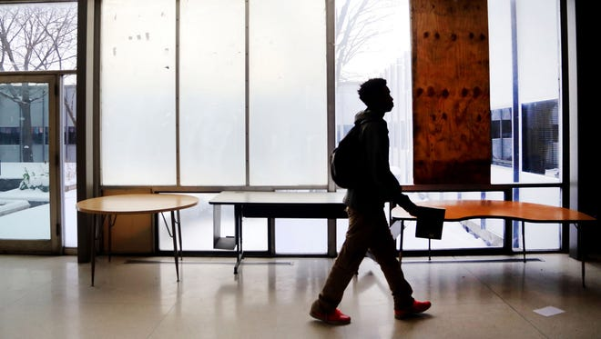 A student of Osborn Evergreen Academy of Design and Alternative Energy in Detroit walks through the hallway past a boarded up window on Thursday, Jan. 14, 2016.Osborn Evergreen Academy of Design and Alternative Energy is one of 25 schools in Detroit that could shut down at the end of the year.