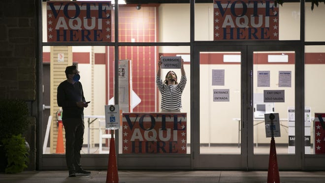 An election worker sets up an early voting location at the Shops at Arbor Walk while a voter waits in line before dawn on Oct. 13, the first day of early voting.
