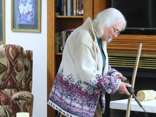 Pictured is Mrs. Ollie Reynolds with an antique tool.